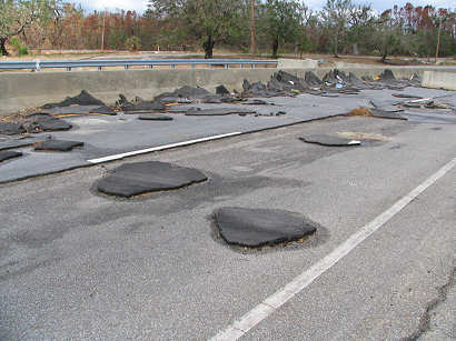 Pavement was peeled off by the storm surge and slapped against the highway barrier - Highway 90