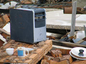 Computer and coffee cups sit untouched in the hurricane debris - Ocean Springs, Mississippi