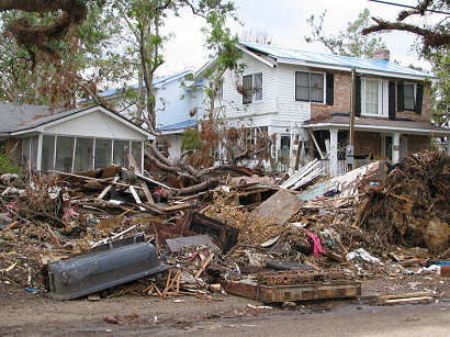 Huge mountains of debris almost hide the ruined houses behind - Ocean Springs, Mississippi