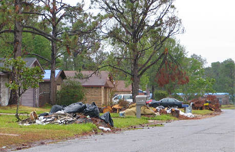 trash piled outside of hurricane damaged homes
