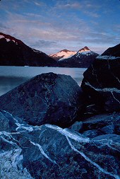You can see the echoing patterns of the glaciers within the agate markings in the larger boulders in the foreground, Portage Lake, Alaska, photograph by Brent VanFossen