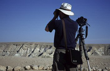 Brent wears a hat while photographing out in the desert sun, photograph by Lorelle VanFossen