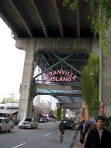 granville island entrance with bike riders by lorelle vanfossen