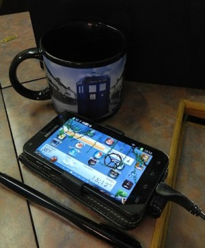 Cell phone on desk next to coffee mug with Doctor Who logo - photography by Lorelle VanFossen.