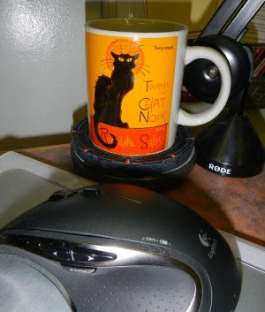 Cup with cat on it sitting on a Stargate Coaster next to computer mouse on desk - photography by Lorelle VanFossen.