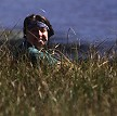 Lorelle sites in the grasses as spotter for eagles, British Columbia, Canada.
