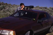 Brent VanFossen balances his long camera lens on roof of car while photographing big game animals from the road. Photography Lorelle VanFossen.