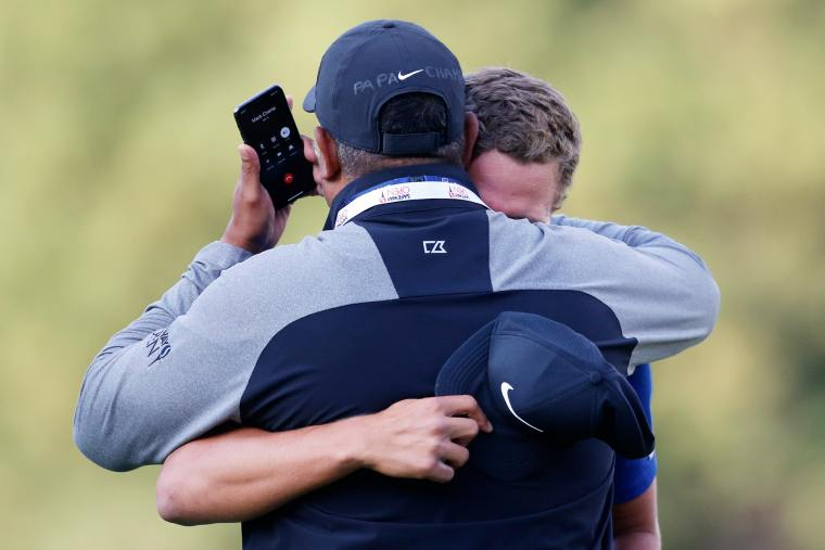 Cameron Champ hugs Jeff Champ while on phone with Mack Champ after winning Safeway Open