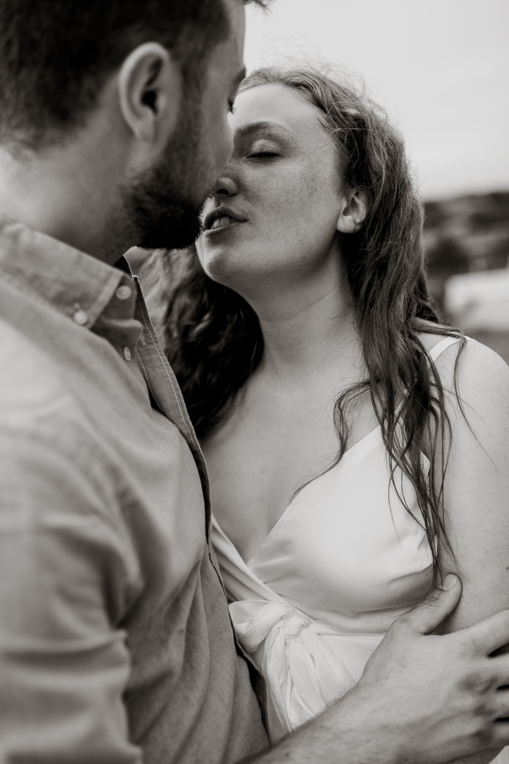 Couple on the beach in the water romantic engagement session black and white Carolina camille camacho photography