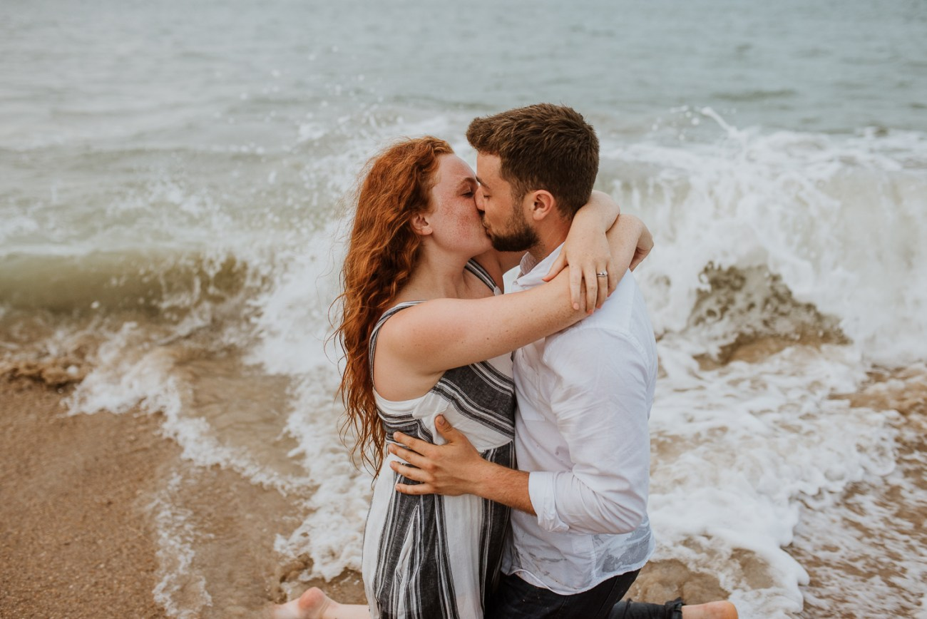 Couple kissing in the ocean romantic engagement session avon North Carolina camille camacho photography