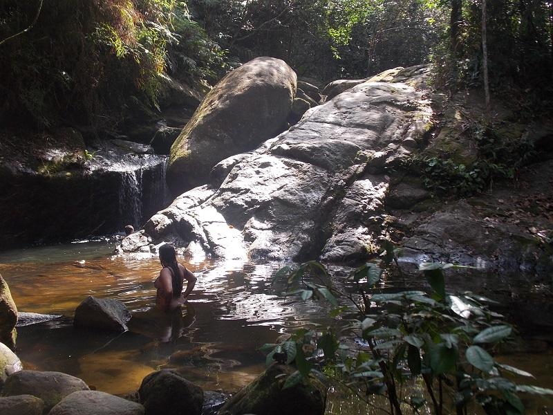 trindade e suas belezas naturais foto de pessoa se banhando em cachoeira - Trindade. Belezas naturais praias e cachoeiras em harmonia.