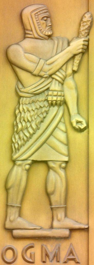 Ogma. Figura de bronze esculpida por Lee Lawrie. Detalhe da porta, entrada leste, Edifício John Adams da Biblioteca do Congresso, Washington, D.C. - Fonte: https://en.wikipedia.org/wiki/Ogma#/media/File:Ogma-Lawrie-Highsmith.jpeg