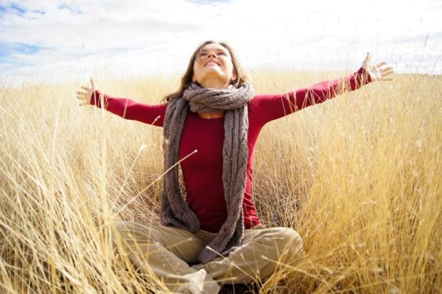 Beautiful young woman enjoying sunshine in a field with long grass