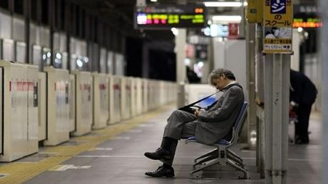 Người lao động ngồi chờ tàu đêm ở Nhật Bản. Ảnh: BBC