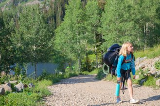 Girl walking on path with backpack.