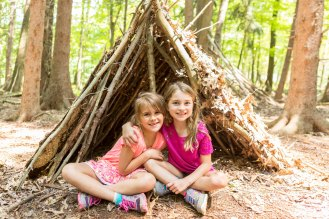 Two girls in front of their outdoor tent built from sticks and leaves