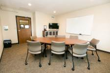 Conference room with conference table, chairs, phone, tv and whiteboard.