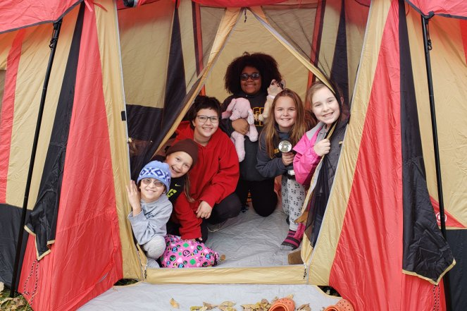 Six Girl Scouts inside their tent.