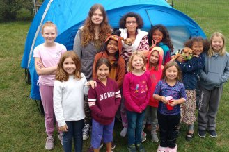 Girl Scout Troop poses for a picture outside their tent.