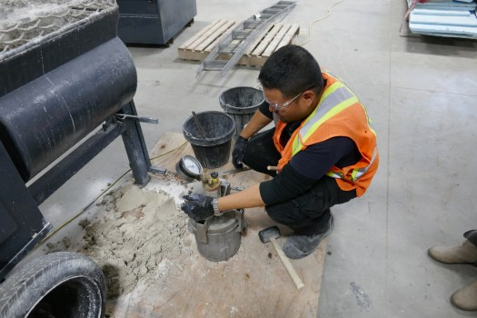 A mason tests for air content in preparation for restoration of deteriorated stones.