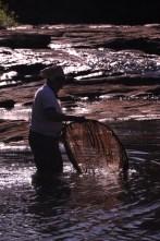 Com apetrecho de pesca tradicional, senhora indígena pesca camarões e curucas no rio de Una, 2012, por Daniela Alarcon.