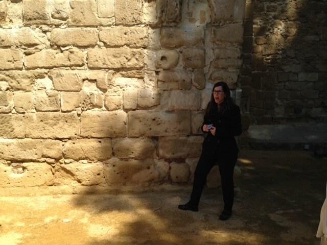 Gids Veronica laat aan de buitenlandse gasten de kogelgaten in de kasteelmuur zien. Deze muur werd in de burgeroorlog als executieplaats gebruikt