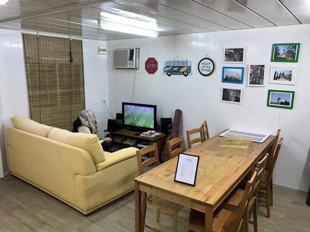 De piepkleine verblijfsruimte van camperplek Cartagena met voetbal op tv én Janine ervoor.