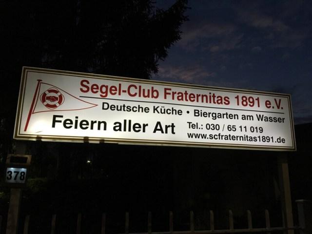 Het uithangbord aan de straatkant met logo en vlag.