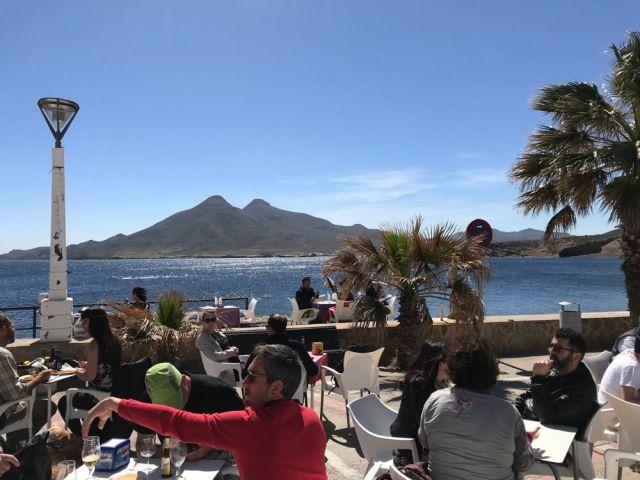 Het restaurantpubliek kijkt vanaf La Isleta del Moro naar de uitgebluste vulkanen bij Los Escullos.