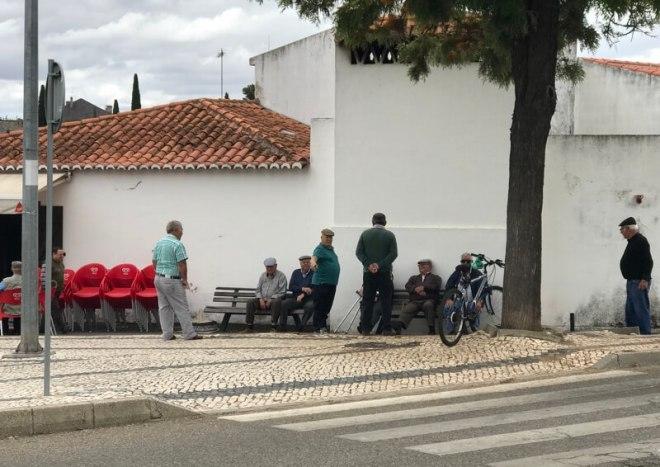 De mannen met de petten zitten op hun eigen leugenbankje in Serpa.