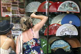Unas turistas observan los abanicos expuestos en un escaparate. Foto: Junta de Andalucía.