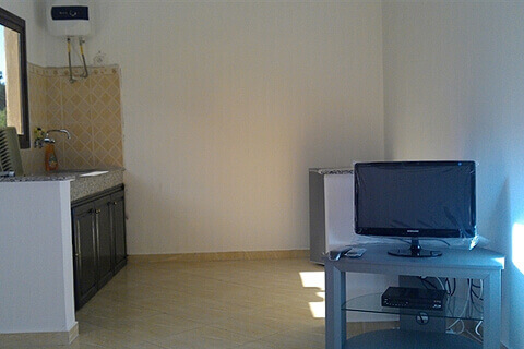 Camping Aourir – A dining room and the kitchen at the Apartments at the Campsite which you can rent