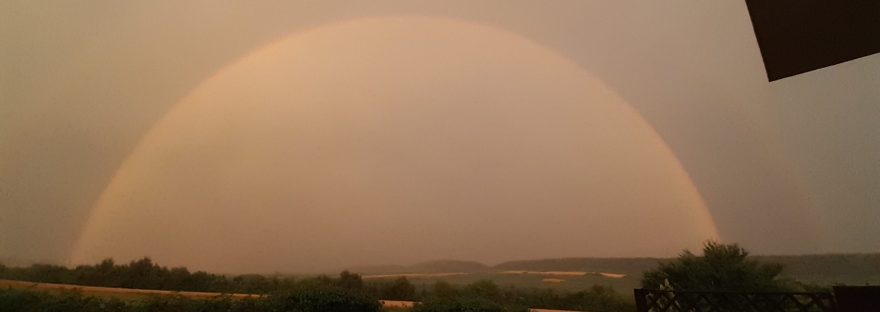 half circle raibnbow over valley in dark storm clouds