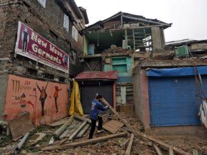 Rapaz tenta retirar destroços que obstruem uma casa em Srinagar, na Índia, após um terremoto ocorrido neste domingo (10/04) – Foto: Danish Ismail/Reuters