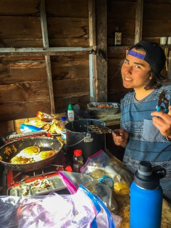 Image of young man preparing breakfast at camp. A Lake Champlain Maritime Museum summer expedition.