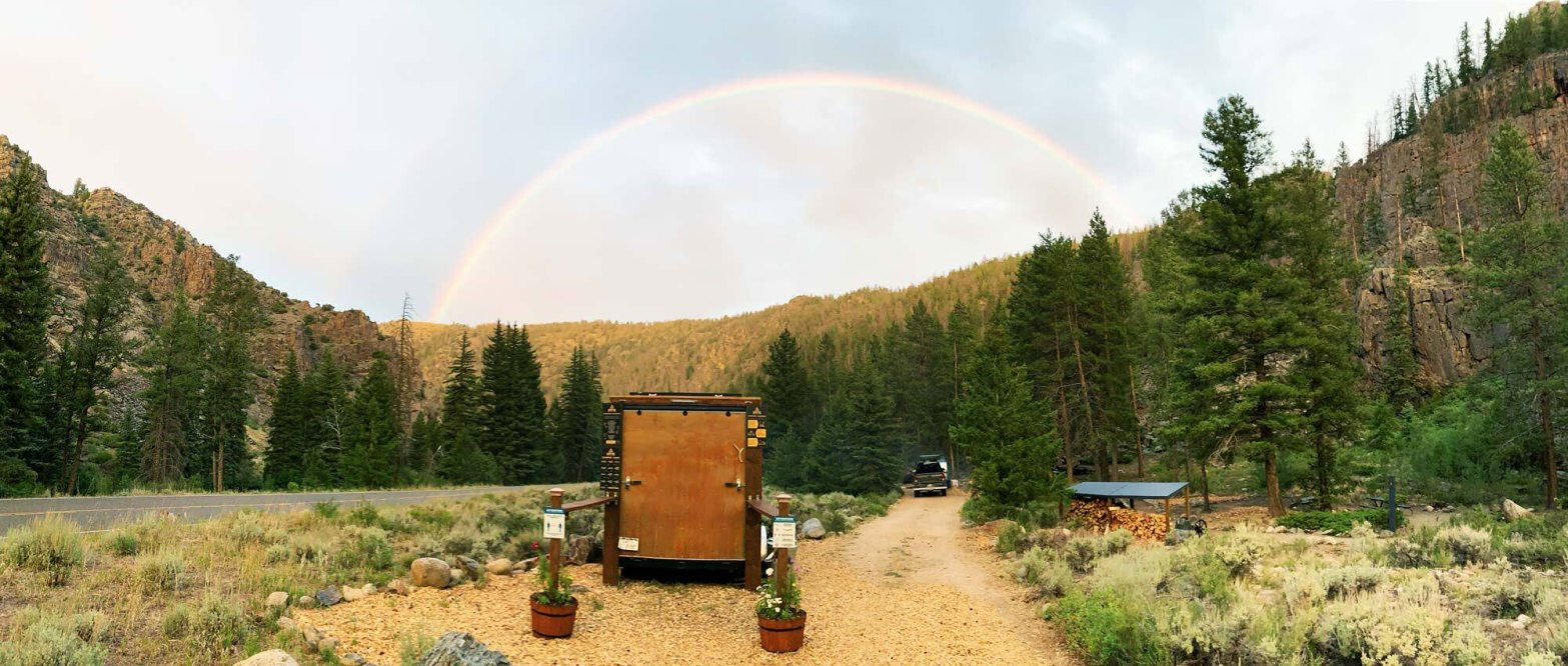 rainbow over pine tree covered hills over dirt road