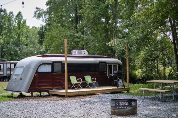 vintage red Spartan trailer at campground with string lights and fire pit