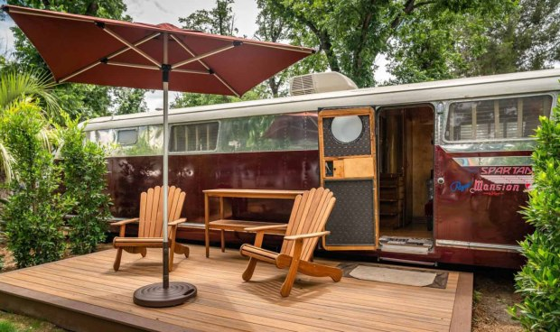 vintage spartan red trailer with wooden deck, Adirondack chairs, and umbrella