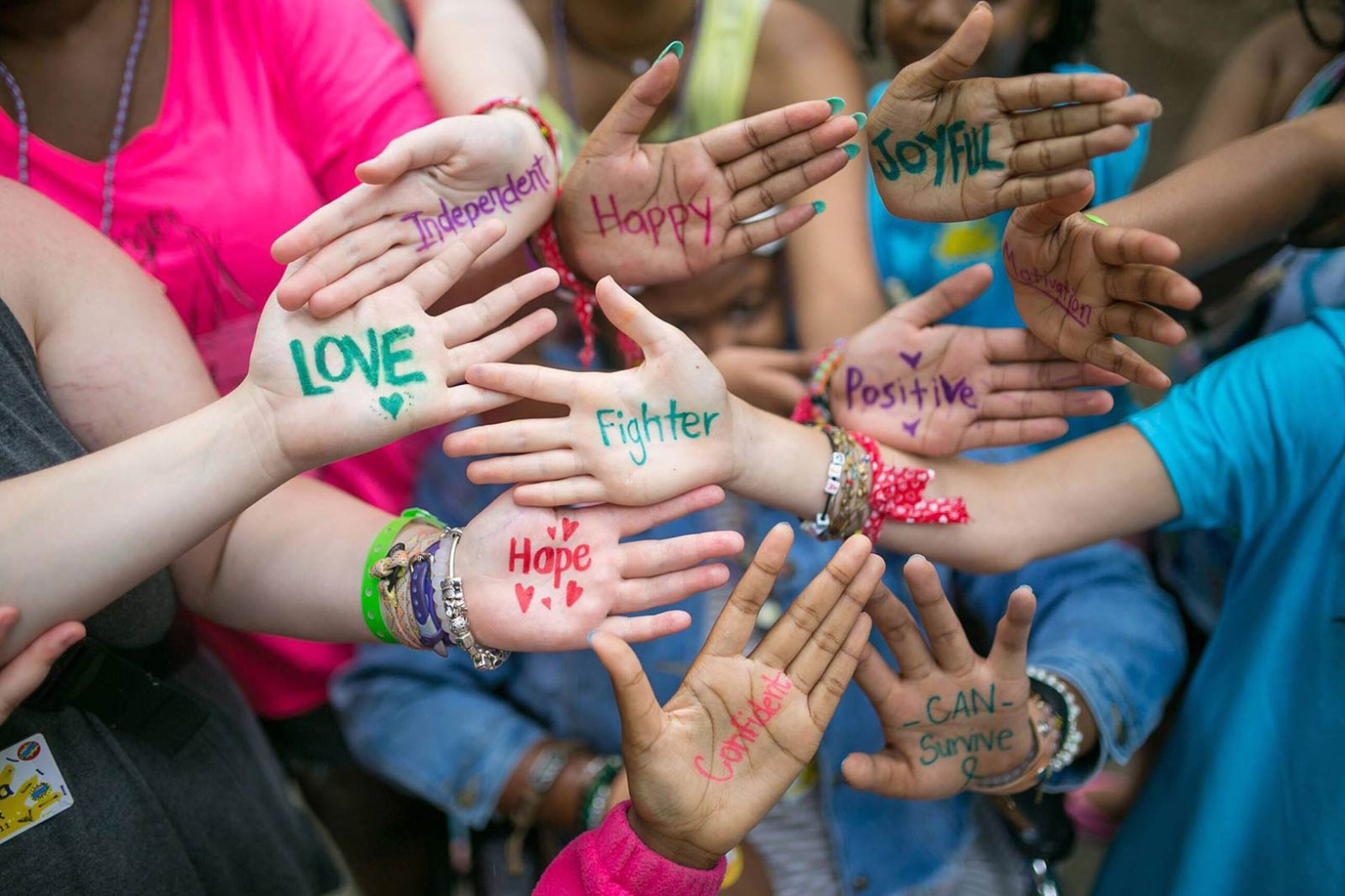 a group of kids hands with written words