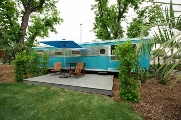 Sky blue vintage camper with wooden deck, umbrella, and adirondack chairs