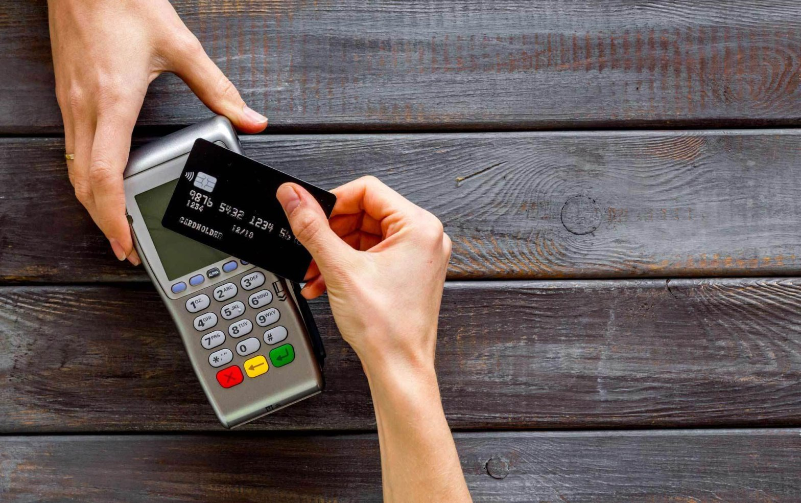 Two hand paying with a credit card and credit card reader
