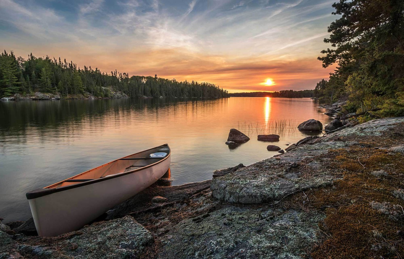 A lone canoe on shore at a peaceful lake at sunset