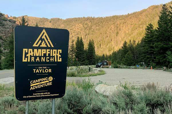campground sign in front of parking lot and hill of trees