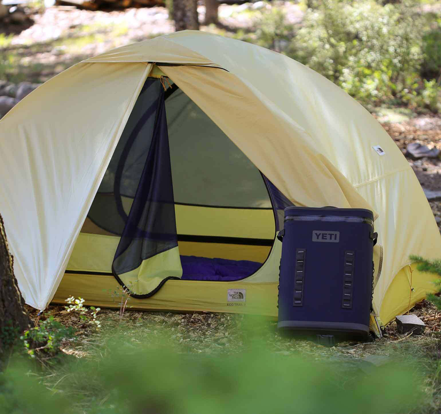 yellow tent in the woods with camping gear