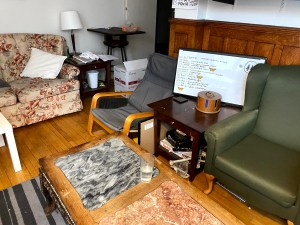 A living room with three chairs and two small tables