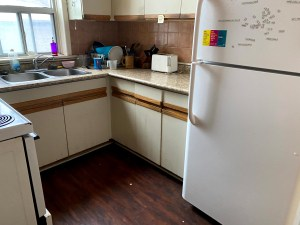 A kitchen with cabinets and a fridge
