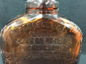 Close up of the embossed federal disclaimer on the bottle recovered by CAP