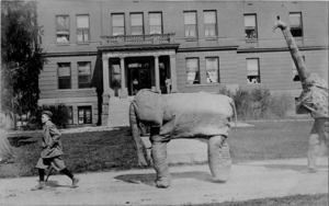 1909 Athletic Carnival. Costumed students marching in front of Morrill Hall.