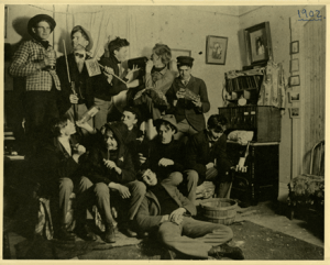Several college friends posing for a photo in an Abbot Hall dorm room, 1901.