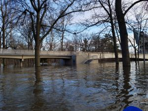 Water levels nearly reaching the bottom of the pedestrian bridge to the library. Image source.